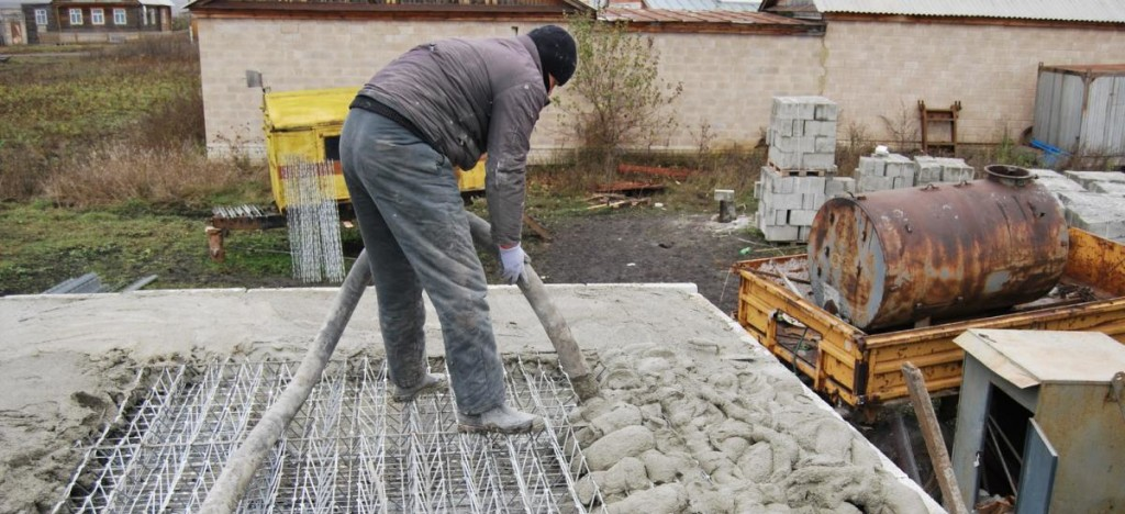рабочий заливает бетон