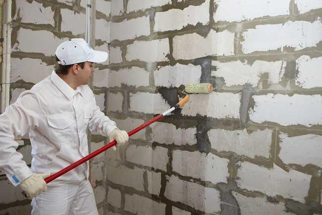 Грунтовать стены можно валиком, а можно налить состав в обычный садовый